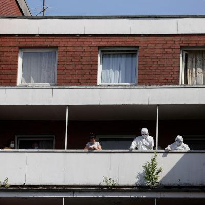 Suojapukuisia ihmisiä sekä asukkaita kerrostalon parvekkeella