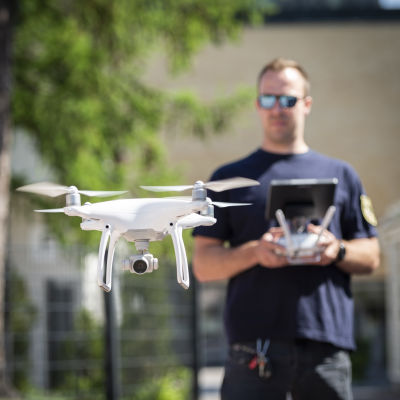 Etualalla drooni lentää. Taaempana droonia lennättävä pilotti Mika Eklund.
