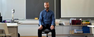 En person sitter på en stol framme i ett klassrum