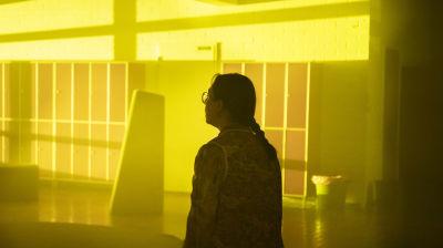 En person står i en tom skolkorridor i dunkelt ljus, i bakgrunden finns förvaringsskåp.