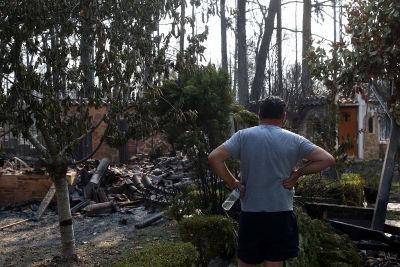 En man tittar på ett nedbrunnet hus efter en skogsbrand i Varybobi i Grekland.