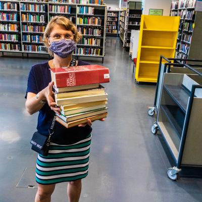 Malin Hollmen med en bunt böcker i famnen.