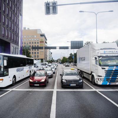 Kuvassa on linja-auto, henkilöauto, taksi ja kuorma-auto Mannerheimintiellä Helsingissä elokuussa 2020.