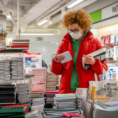 Nainen katselee kalenterita kirjakaupassa hengityssuojain kasvoillaan.