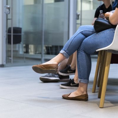 Ihmisiä terveyskeskuksessa odottamassa lääkärille pääsyä