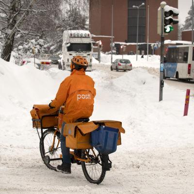 Postinjakaja pyöräilee talvisessa katumaisemassa.