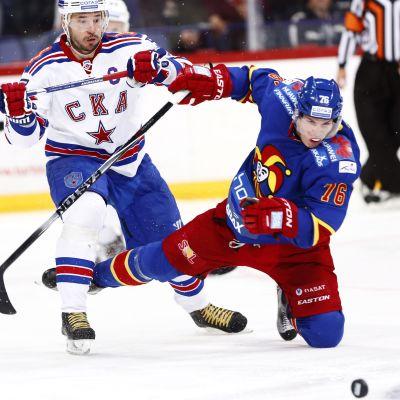 Hockeyspelare faller omkull.