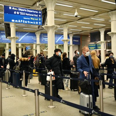 Människor köar i en tågterminal. De bär munskydd och har resväskor i händerna.