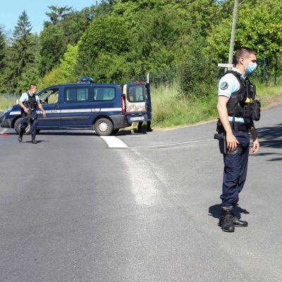 Poliiseja autotiellä metsäisen mäen juurella.