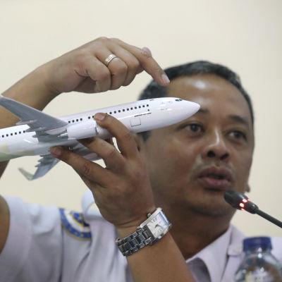 Olycksutredaren Nurcahyo Utomo håller en miniatyr av ett Boeing 737 MAX-plan under en presskonferens om Lion Airs flygolycka.den 28 november.