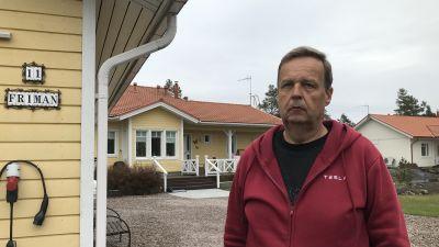 Rune Friman står med ett gult hus i bakgrunden