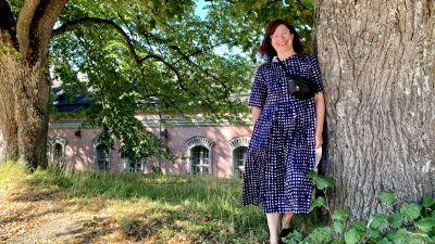 En kvinna med axellångt mörkt hår står lutad mot ett träd. Hon har på sig en blå och vit-prickig klänning, och ser in i kameran och ler.