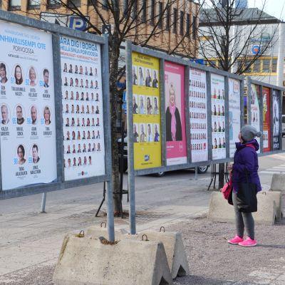 Kvinna studerar valaffischer på trottoar i Borgå.