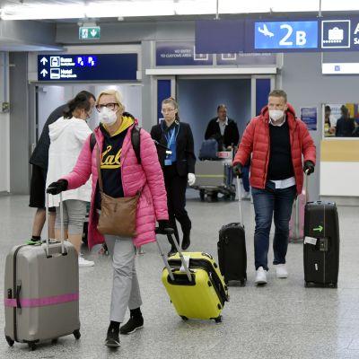 Flygpassagerare med ansiktsskydd drar sitt bagage på flygplatsen.