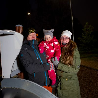 perhe seisoo puistossa