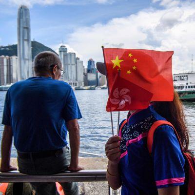 Invånare med Hongkong i bakgrunder som håller upp en kinesisk flagga.