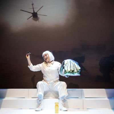 En skådespelare i vitt (Hellen Willberg) leker med ett par solglasögon medan en stridshelikopter och soldater projiceras på väggen bakom henne.