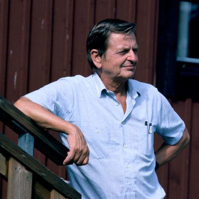 Sveriges premiärminister Olof Palme lutar ena armen mot ett trappräcke framför en rödmålad stuga.