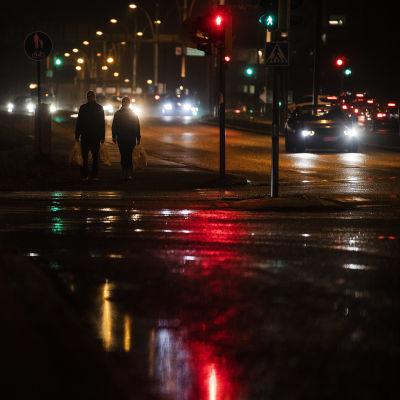 Kaksi ihmistä ylittää kadun Munkkiniemessä Helsingissä marraskuussa 2020.