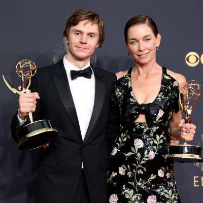 Evan Peters och Julianne Nicholson poserar med sina Emmystatyetter. Evan bär en svart kostym och svart fluga. Julianne har på sig en svart klänning med blommönster.