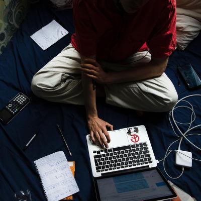 Nuori opiskelee huoneensa sängyllä.
