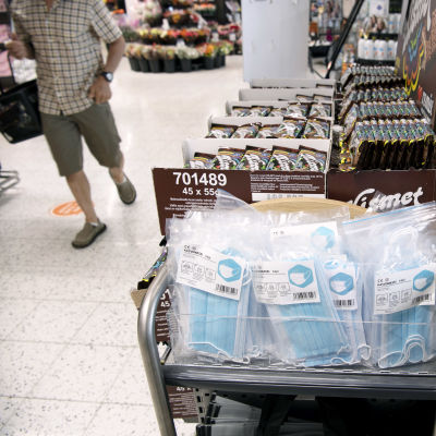 Kasvomaskeja myynnissä kaupan kassan edustalla.