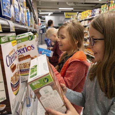 oppilaat tutkivat muropaketteja kaupassa