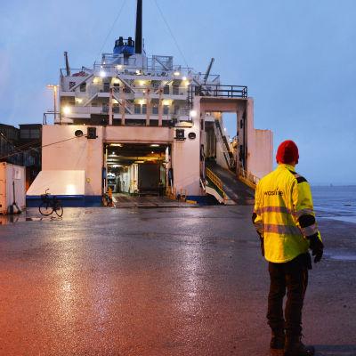 Satamatyöntekijä punaisessa pipossa ja huomioliivissä satama-alueella, laiva taustalla