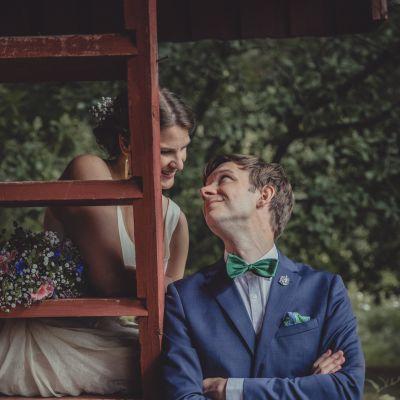 Bröllopsfoto av Fanny och Leo Johansson-Stockford. Fanny sitter på en stege och Leo står bredvid. De tittar ömt på varandra.