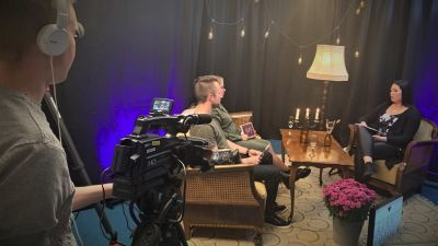 En ung man filmar i en tv-studio där två personer intervjuar en kvinna i fotölj