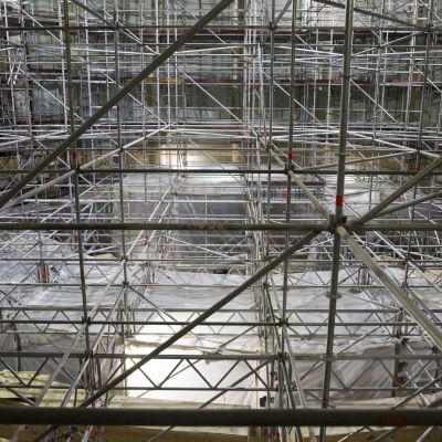 Riksdagens plenisal fylls av byggnadsställningar.