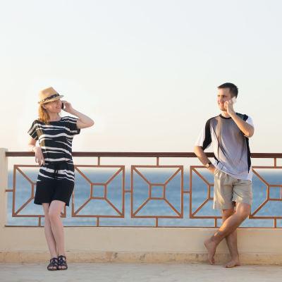 Kvinna och man står vid havet på några meters avstånd från varandra och talar i telefon