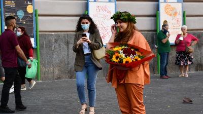 En ung kvinna i orange sidenkostym håller en stor bukett blommor i handen. Hon har också en bladkrans på huvudet.