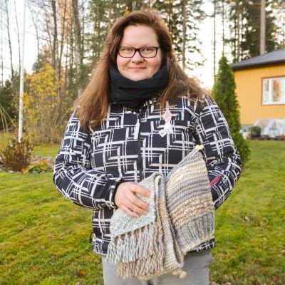 En kvinna som står utanför sitt hus och håller sina handarbeten i handen.