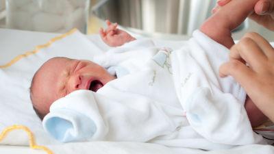 Spädbarn och en vuxen persons händer