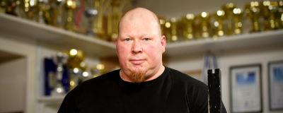 Ove LEhto poserar framför en enorm rad av pokaler och priser i sitt gym