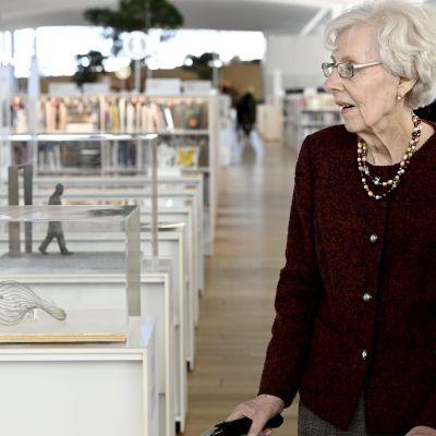 Tellervo Koivisto tittar på miniatyrskulpturen.