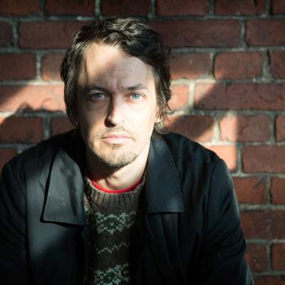 Regissören Johannes Nyholm poserar sittande farmför en tegelvägg.