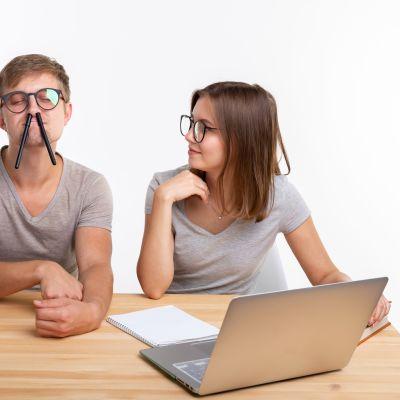 Man och kvinna sitter vid bord, hon försöker visa honom något på datorn men han spexar med pennor i näsan