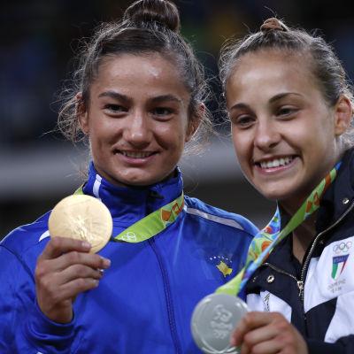 Två judokor poserar med guld- och silvermedaljer från OS.