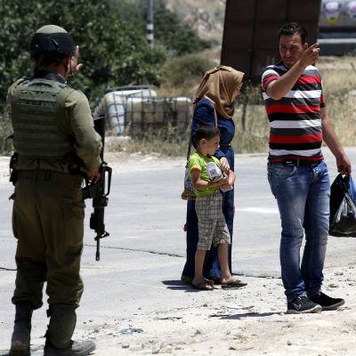 En palestinsk familj vid en israelisk vägspärr på Västbanken torsdagen 9.6.2016