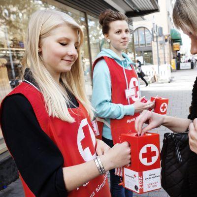 kvinna lägger en slant i insamlingsbössa för hungerdagsinsamlingen