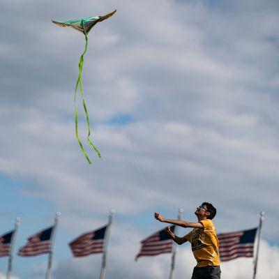 En pojke flyger drake. I bakgrunden syns USA:s flaggor.