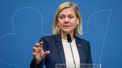 Magdalena Andersson i blå kavaj bakom ett podium med mikrofon.