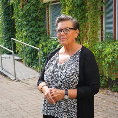 Kvinna med kort hår och glasögon står framför en gul byggnad.