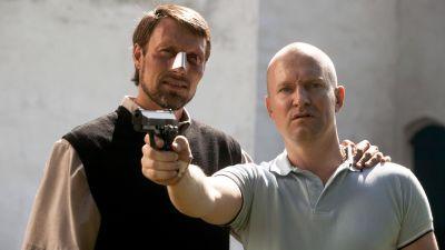 Prästen Ivan (Mads Mikkelsen) står bredvid Adam (Ulrich Thomsen) som håller en pistol i handen och ser förvirrad ut.
