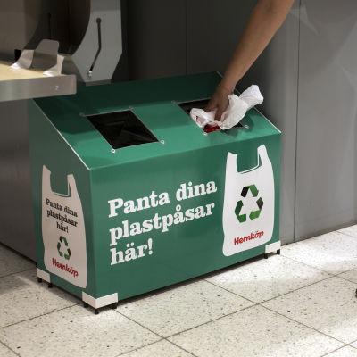 """En grön papplåda med texten """"Panta dina plastpåsar här!"""""""