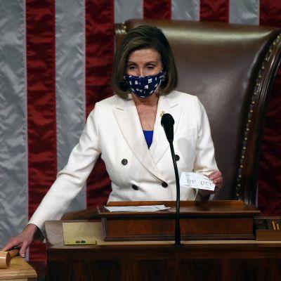Nancy Pelosi sträcker sig mot klubban för att rösta igenom en lag i USA:s representanthus.