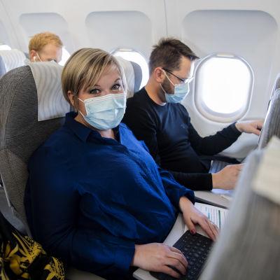 Kuvassa lentokoneessa maskit kasvoillaan ovat Annika Saarikko ja Erkki Papunen.