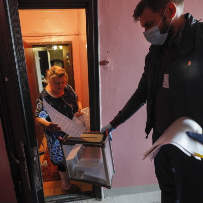 En kvinna står i sin dörröppning och lägger ner sin röst i en urna som en man håller fram.